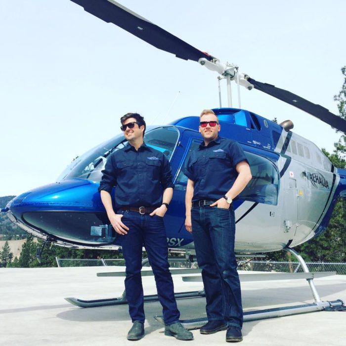 2 Valhalla helicopter pilots pose in front of their Bell heli