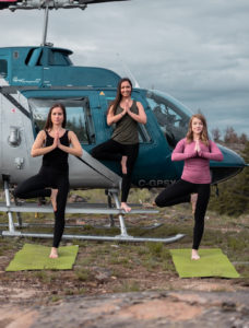 Three women do yoga poses with helicopter