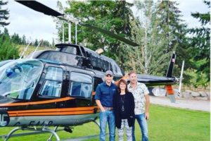 Mother and adult sons outside helicopter